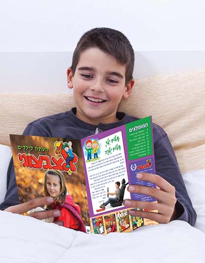 child in bed reading a book happy